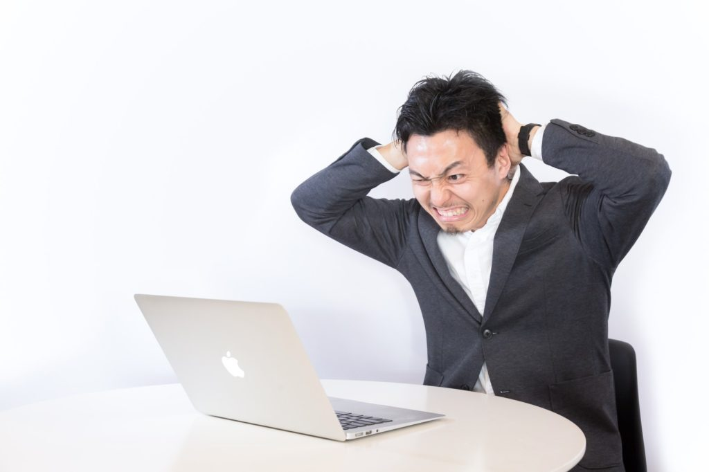 パソコン画面を見てショックを受けている男性
